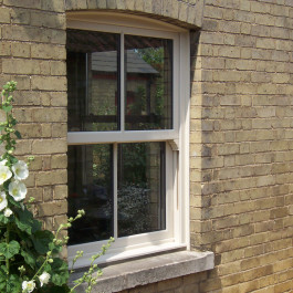 A sliding sash window with an arched top in cream