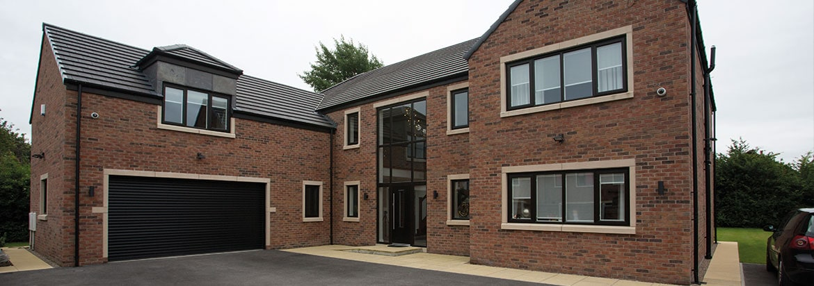 Front of a house with dark grey window frames