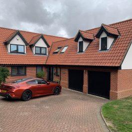 House with grey casement windows, black composite door and black garage doors