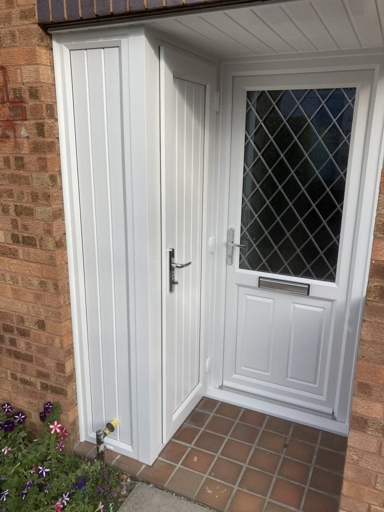 white uPVC door with leaded glazing and a white uPVC panelled door leading to a bin storage area.